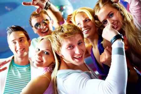 adolescentes riendo: Retrato de hombre feliz y chica bailando en la fiesta con los amigos en el fondo