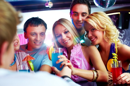 Photo of pretty girls looking at barman with guys near by photo
