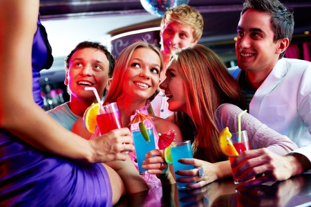 Photo of pretty girls and guys looking at one of their friends sitting on the bar photo