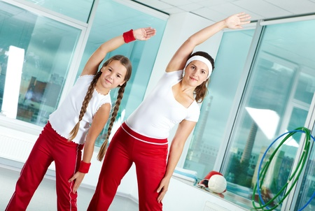 Portrait of healthy female and her daughter practicing physical exercise photo