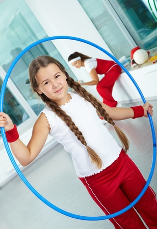 Portrait of healthy girl with blue hoop in gym photo