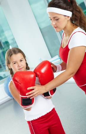 Portrait of pretty female touching her daughter in boxing gloves photo