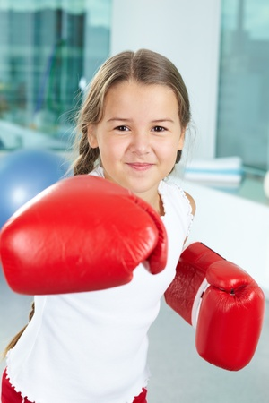 female boxer: Portrait of pretty girl in boxing gloves in the gym