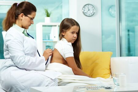 clinician: Portrait of serious clinician treating sick girl with stethoscope Stock Photo