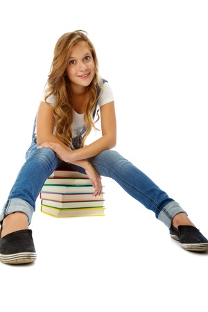 Pretty teenager on heap of books smiling at camera in isolation photo
