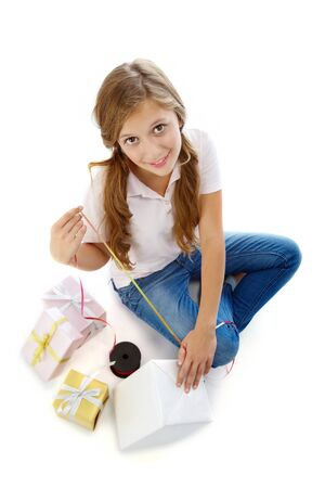 Pretty teenager with giftboxes looking at camera in isolation photo