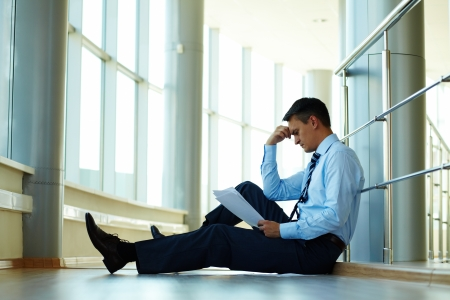 Portrait of serious businessman sitting on the floor while reading paper photo