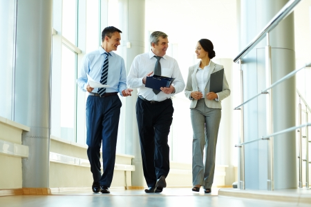 business consulting: Confident business partners walking down in office building and discussing work