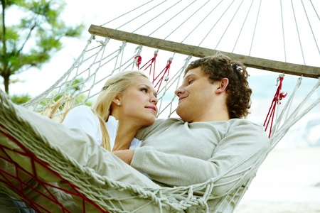 a pair of: Happy dates looking at each other and smiling while lying in hammock