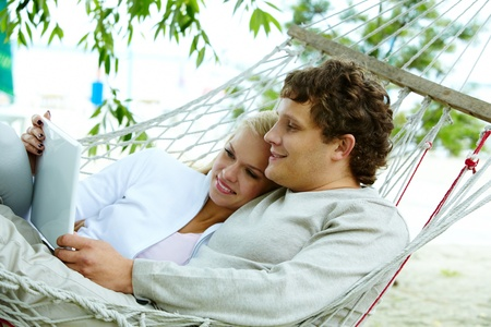 Happy dates with laptop lying in hammock photo