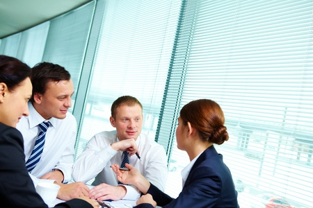 co workers: Image of confident colleagues interacting at meeting Stock Photo