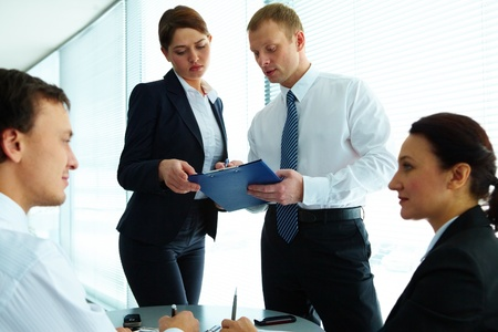 Image of confident colleagues communicating in office photo