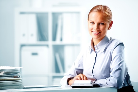Portrait of a young happy businesswoman looking at camera in office photo