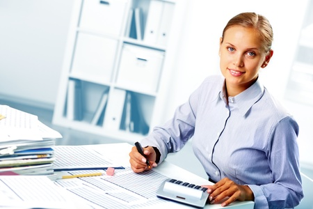 Portret van een jonge gelukkige zakenvrouw kijken camera terwijl het werken in het kantoor