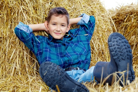 Happy lad lying on hay in countryside photo