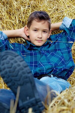 Handsome lad lying on hay in countryside photo