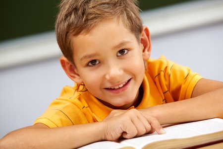 Portrait of smart lad looking at camera during reading lesson photo