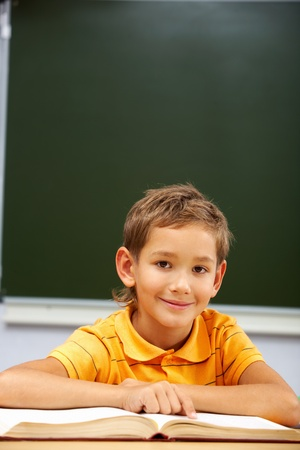 Portrait of happy schoolboy looking at camera during reading lesson photo