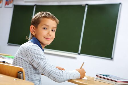 Portrait of smart lad at his place looking at camera during lesson Stock Photo