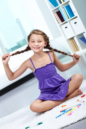 pigtails: Portrait of young smiling child with pigtails posing in front of camera   Stock Photo
