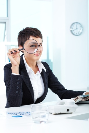 Photo of pretty businesswoman looking at camera through spy glass photo