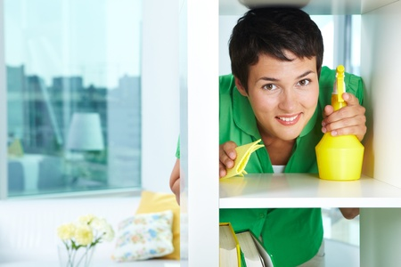 single shelf: Photo of young woman dusting and looking at camera