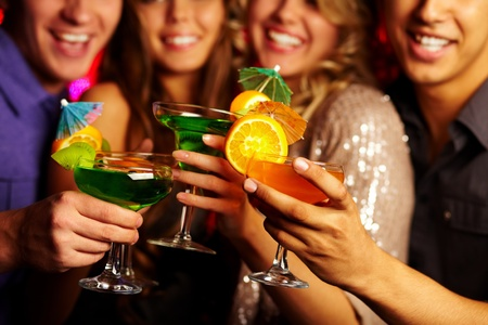 celebratory event: Close-up of several cocktails in young people hands Stock Photo