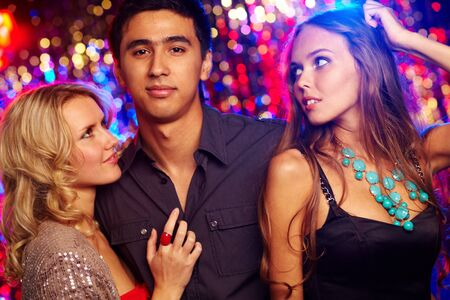 macho man: Image of happy girls and guy clubbing together at party Stock Photo