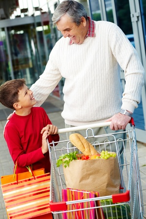 Portrait of grandfather and grandson with goods near supermarket photo