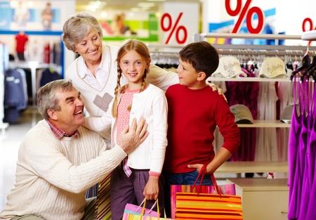 Portrait of happy grandparents and grandchildren in clothing department photo