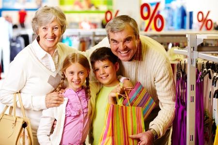ni�os de compras: Retrato de felices abuelos y nietos compra