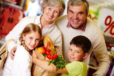 Portrait of happy grandparents and grandchildren holding package with food photo
