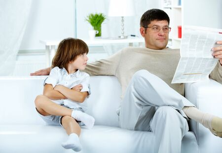 Photo of cute boy looking at his father reading paper at home Stock Photo - 10643909