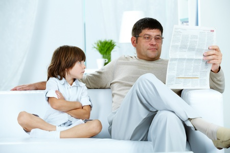 Photo of annoyed boy looking at his father reading paper at home Stock Photo - 10643864
