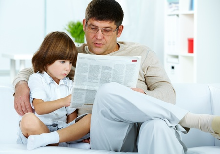 Photo of cute boy and his father reading newspaper together at home photo
