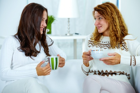 Photo of pretty woman and her teenage daughter having tea at home