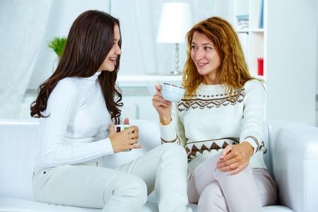 niños platicando: Foto de linda mujer y su hija adolescente tener té en casa Foto de archivo