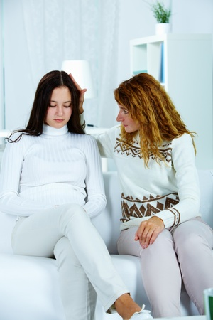 communicate: Photo of pretty woman reassuring her sad daughter