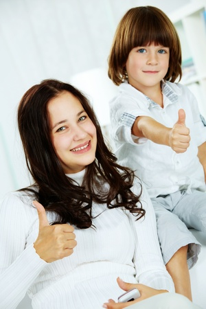 Photo of attractive teenager and her little brother showing thumbs up photo