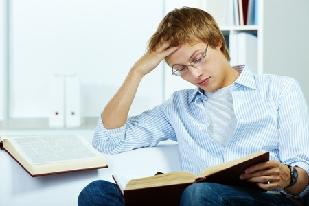 Image of serious student reading book photo