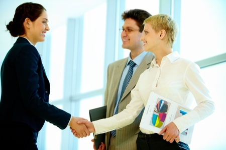 Photo of successful business partners handshaking at meeting photo