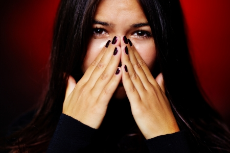 Image of young woman with dark hair drying her tears photo