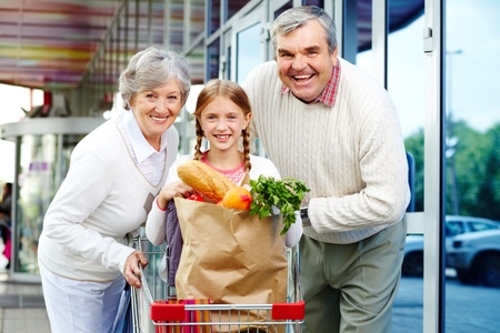 Portrait of happy grandparents and granddaughter near supermarket photo