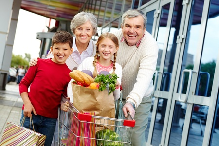 grandparents: Portrait of happy grandparents and grandchildren near supermarket