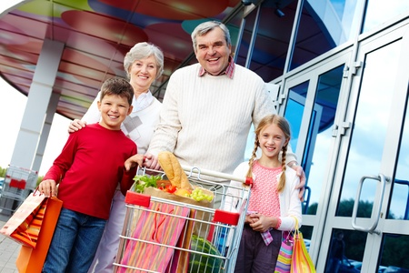 Portrait of happy grandparents and grandchildren with package of food near supermarket photo