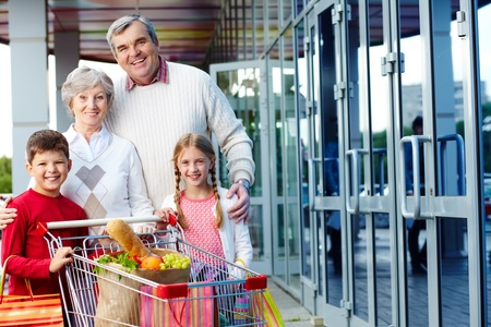 Portrait of happy grandparents and grandchildren with package of food near supermarket Stock Photo - 10664380