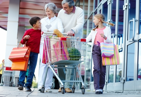 woman shopping cart: Portrait of happy grandparents and grandchildren walking and chatting after shopping Stock Photo