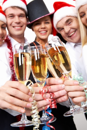 Image of crystal glasses full of champagne held by happy business people photo