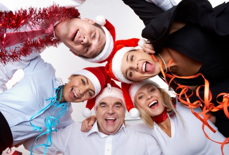 company party: Portrait of smart colleagues in Santa caps wishing you Merry Christmas