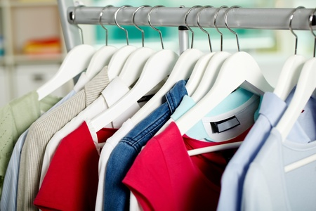 Photo of hangers with different clothes in department photo